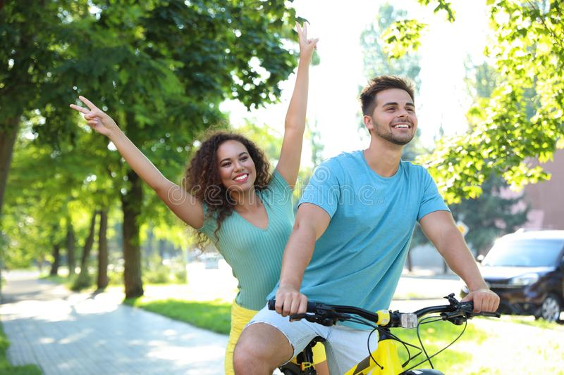 Happy young couple riding bicycle stock photo