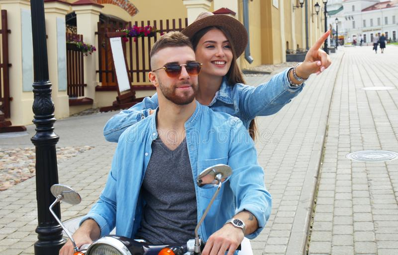 Happy young couple riding scooter in town. Handsome guy and young woman travel. Adventure and vacations concept. royalty free stock images