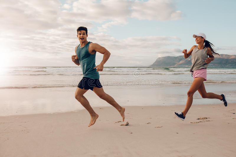Happy young couple of runners on the beach. Full length shot of fit young men and women running on the beach. Happy young couple of runners on the sea shore stock photos
