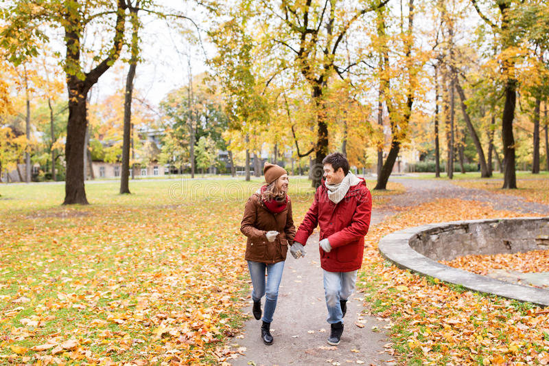Happy young couple running in autumn park stock image