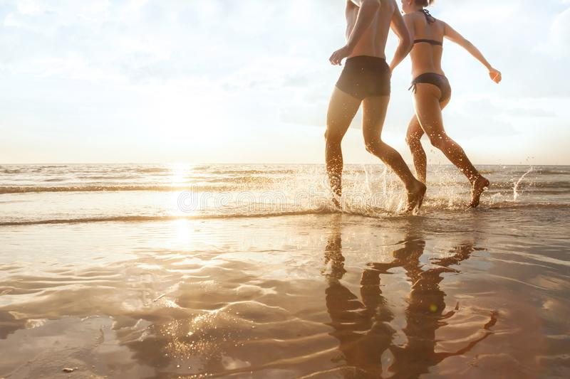 Happy young couple running to the sea on the beach at sunset, silhouettes of man and woman royalty free stock photography