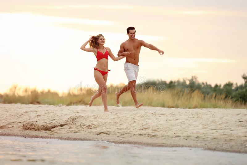 Happy young couple running together on sea  at sunset stock photo