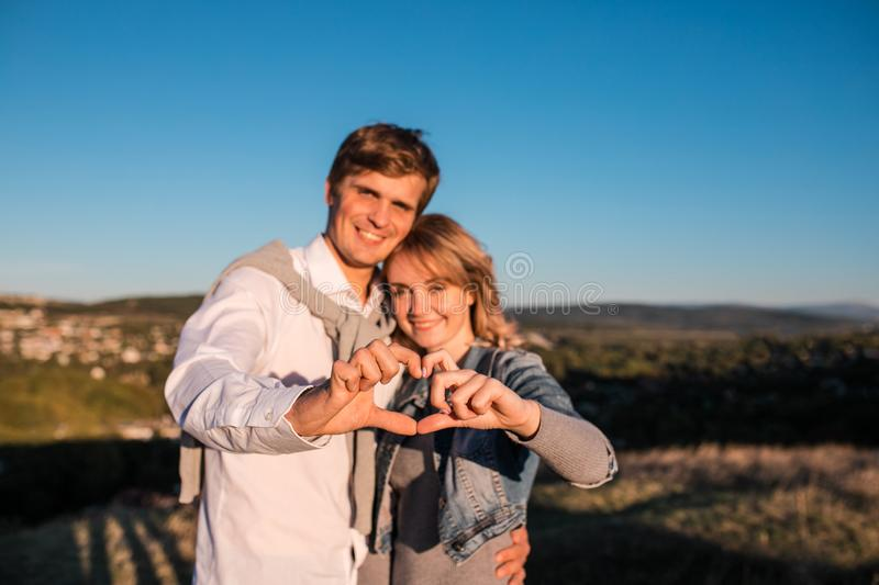 Happy young couple`s making heart of fingers. stock image