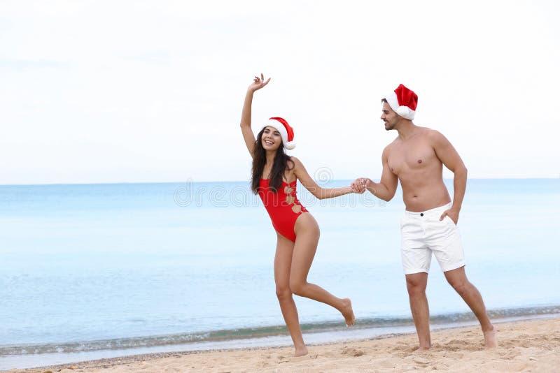 Happy young couple with Santa  on beach near sea. Happy young couple with Santa hats on beach near sea royalty free stock photos