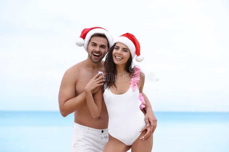 Happy young couple with Santa hats together. On beach stock photos