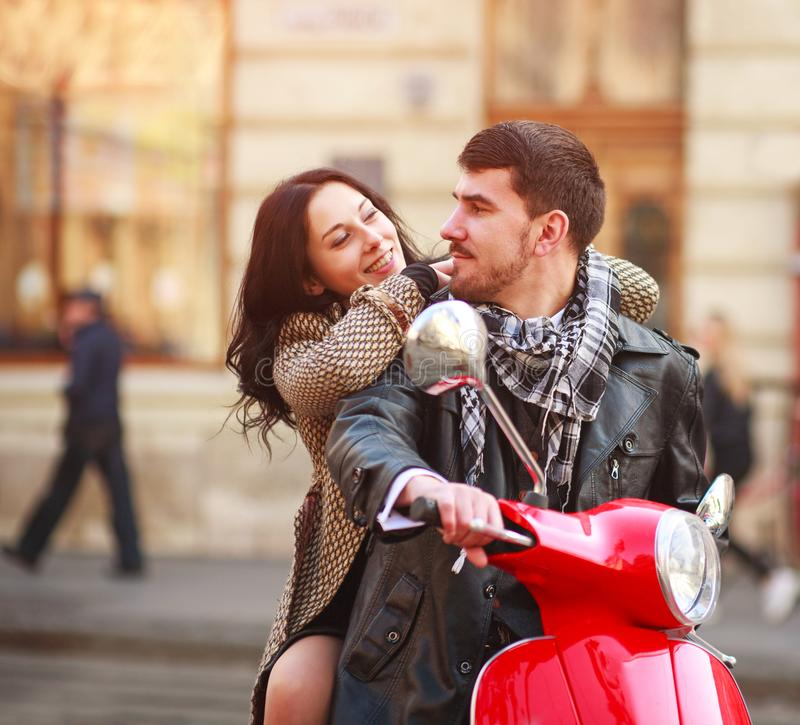 Happy young couple on scooter bike in autumn city together stock photo