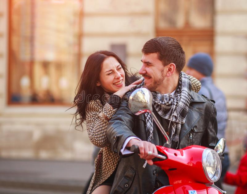 Happy young couple on scooter bike in autumn city together royalty free stock photography