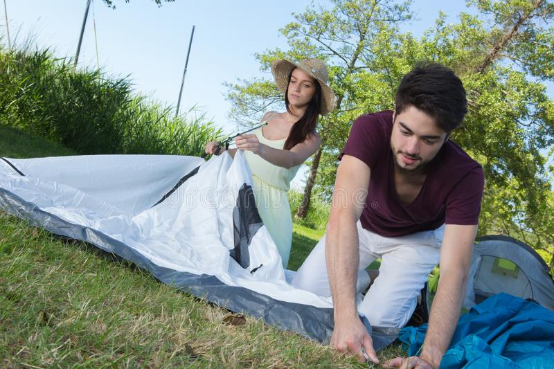Happy young couple setting up their tent at camping site stock images