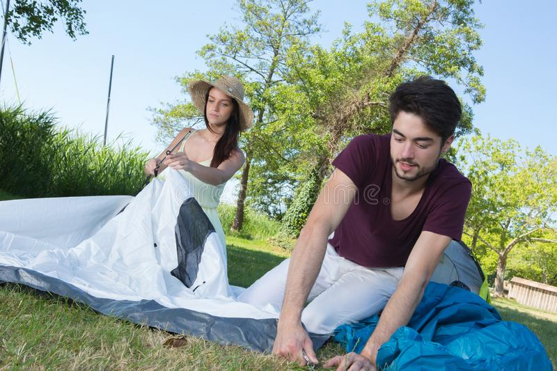 Happy young couple setting up their tent at camping site royalty free stock photos