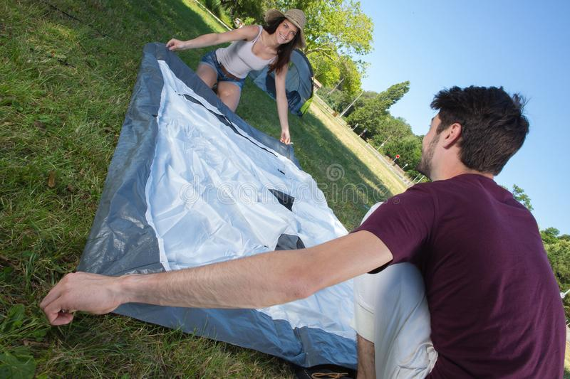 Happy young couple setting up their tent at camping site royalty free stock photography