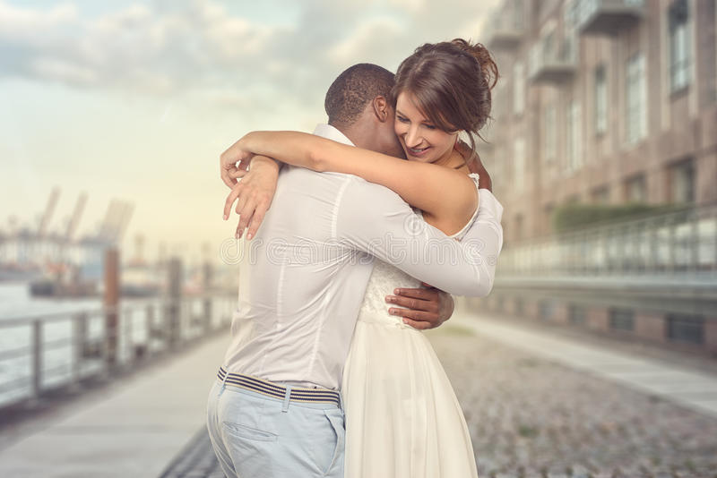 Happy young couple share a special moment. Happy romantic young couple share a special tender moment hugging each other as they show their love and affection stock photos