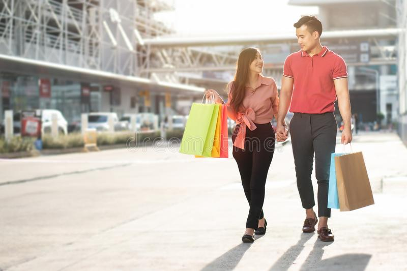 Happy young couple of shoppers walking in the shopping street towards and holding colorful shopping bags in hand. Concept of sale royalty free stock photography