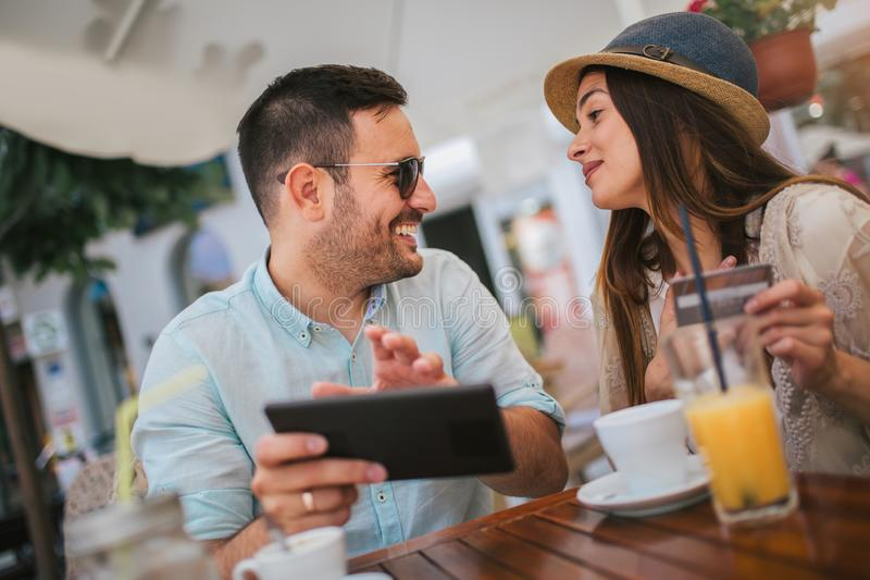 Young couple shopping online while sitting in a cafe. Happy young couple shopping online while sitting in a cafe royalty free stock photos