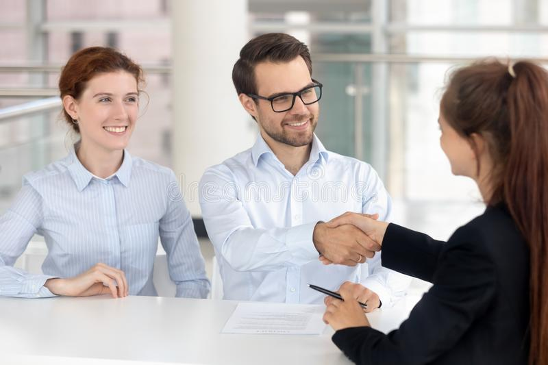 Happy young couple signing mortgage insurance investment contract handshake broker. Realtor insurer, smiling services buyers shake hand of bank agent saleswoman royalty free stock photos