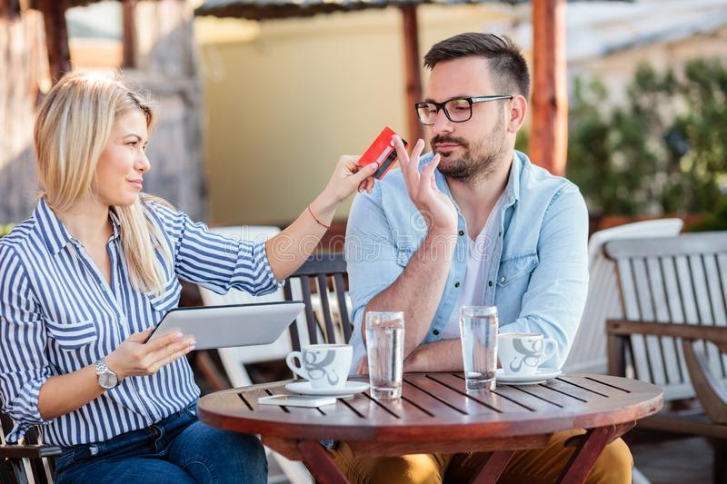 Happy young couple sitting in a cafe and shopping online stock photography