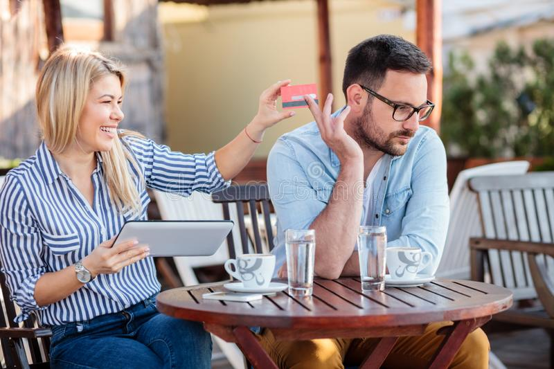 Happy young couple sitting in a cafe and shopping online. Woman taking credit card from her boyfriend. Happy young couple shopping online, sitting in a cafe stock images