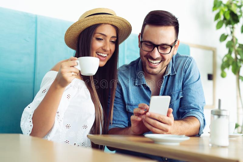 Happy young couple sitting at the cafe table drinking coffee and looking at mobile phone royalty free stock image