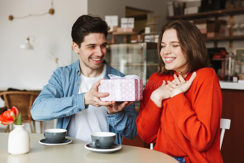 Happy young couple sitting at the cafe table royalty free stock image