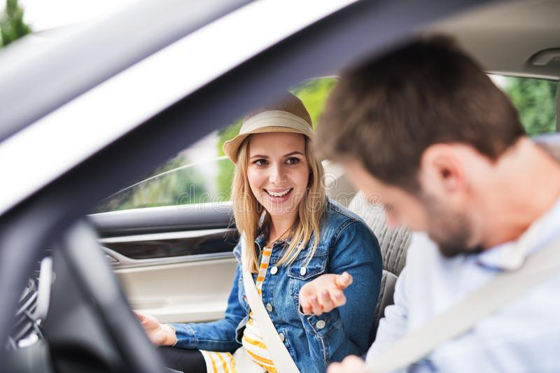 Happy young couple sitting in car, talking. royalty free stock photo
