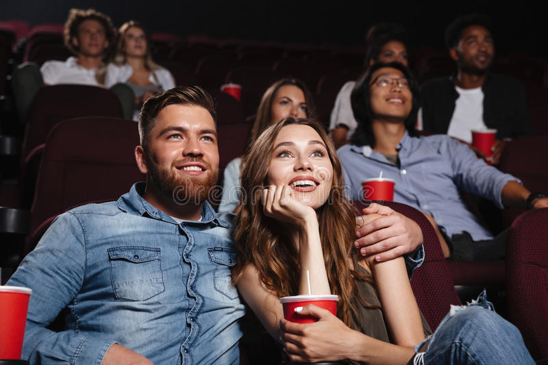 Happy young couple sitting at the cinema royalty free stock photo