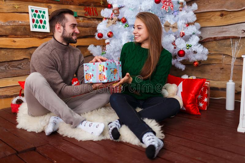 Happy couple sitting under a Christmas tree and giving gift boxes. Indoors. royalty free stock photo