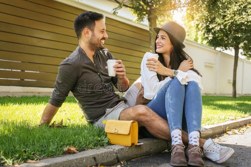 Happy young couple sitting in the park. stock images