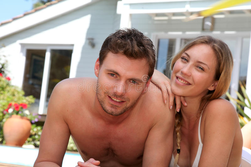 Happy young couple sitting by the pool royalty free stock image