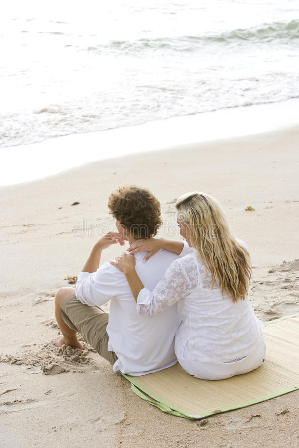Happy young couple sitting together on beach stock image
