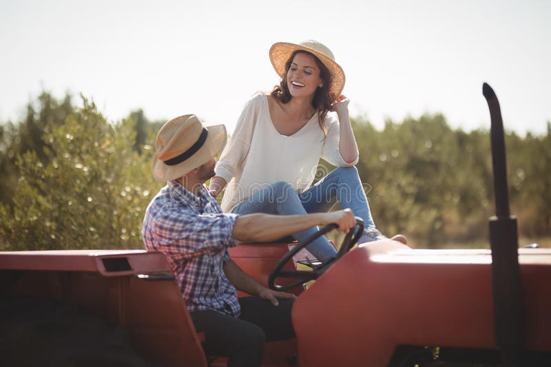Happy young couple sitting together on tractor royalty free stock images