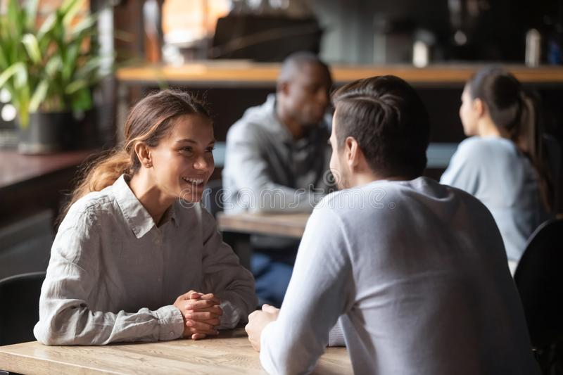 Happy young couple smiling chatting sitting at cafe table royalty free stock image