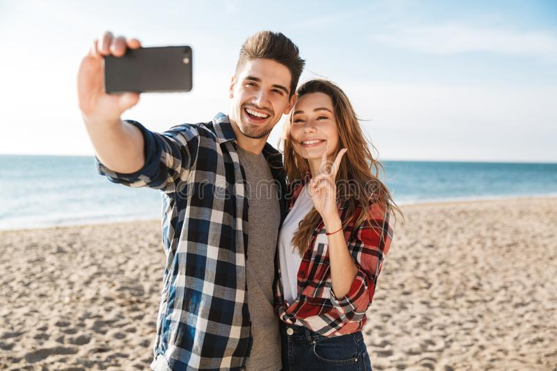 Happy young couple spending fun time. At the beach, taking a selfie with mobile phone royalty free stock image