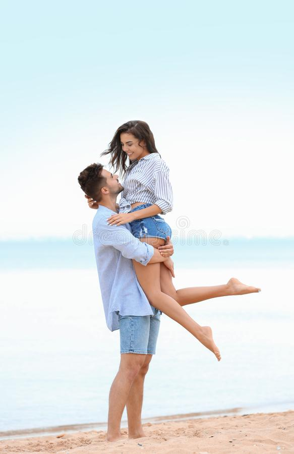Happy young couple spending time  on beach near sea royalty free stock photos