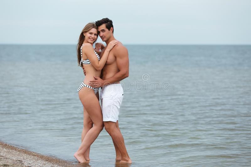 Happy young couple spending time  on sea beach. Space for text royalty free stock photos