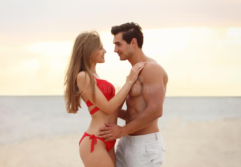 Happy young couple spending time  on sea  at sunset stock image