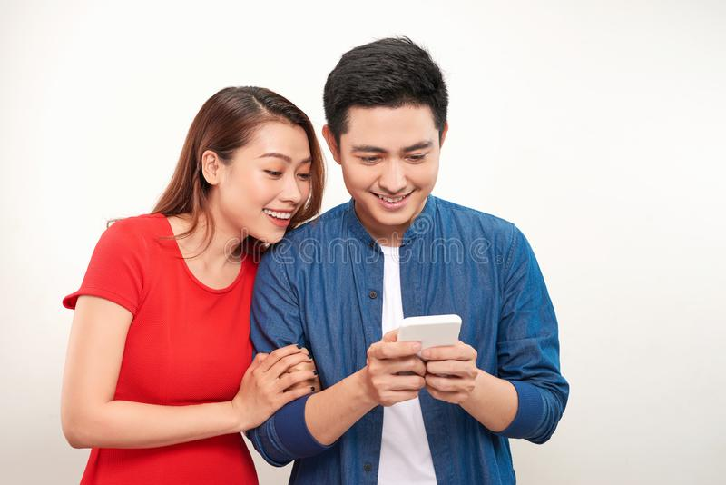 Happy young couple standing behind white background and using their phones stock photo