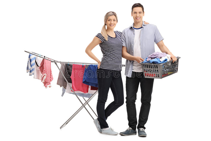 Happy young couple standing in front of a clothing rack dryer royalty free stock photo