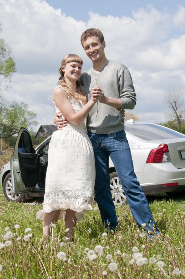 Happy young couple standing near the car stock photos