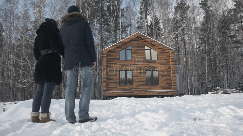 Happy young couple standing near wooden cottage. Stock. Couple stands near the house in the forest in winter stock photos