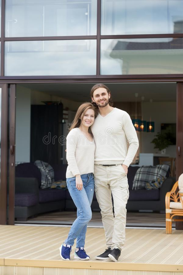 Happy young couple standing on new luxury house terrace, portrai royalty free stock photo