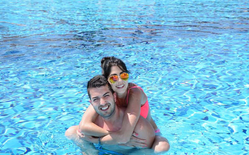 Happy young couple having fun in a pool. Happy young couple on summer vacation royalty free stock image