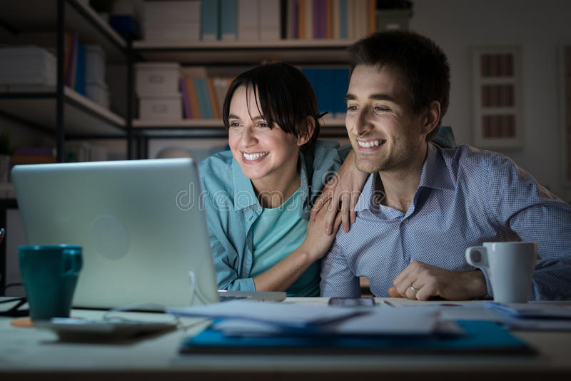Happy young couple surfing the web at home stock photo