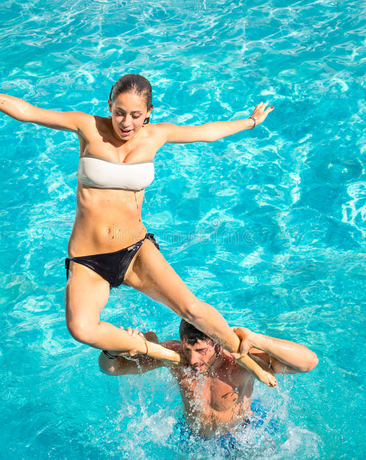 Happy young couple in swimming pool jumping from the shoulder. Concept of love and fun with joyful moments in summer - Vacation lifestyle in exclusive hotel royalty free stock photography