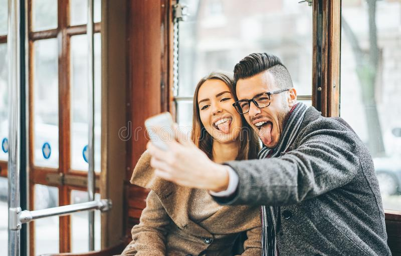 Happy young couple taking photos using mobile smart phone camera inside bus - Travel lovers making a self portrait royalty free stock photos