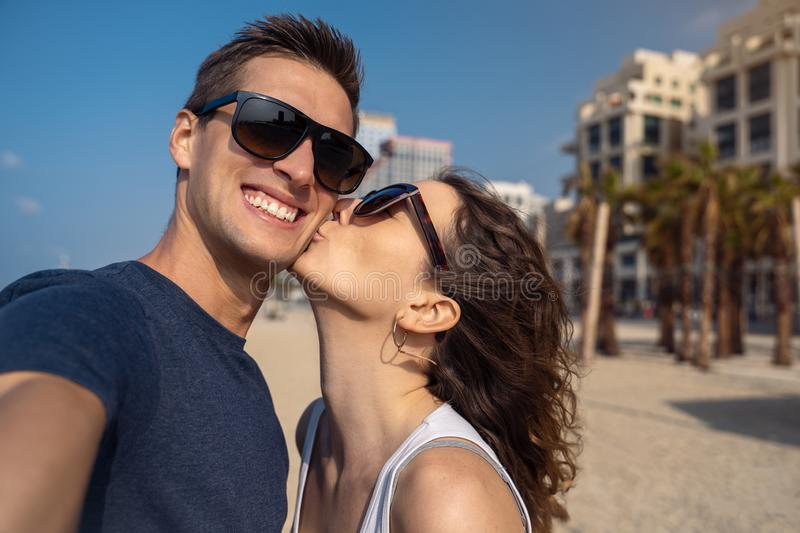 Happy young couple taking a selfie on the beach in Tel Aviv. Couple taking a selfie on the beach, women kissing his boyfriend stock image