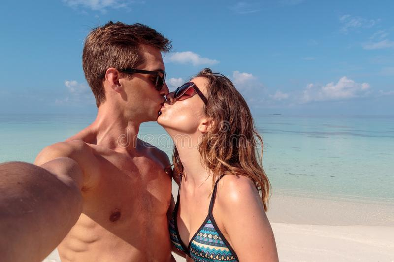 Happy young couple taking a selfie, clear blue water as background. Girl kissing his boyfriend. Man and women in .swimsuit taking a self portrait picture during stock photography