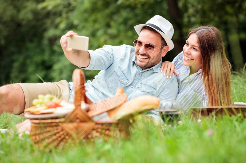 Happy young couple taking a selfie while enjoying picnic time in park royalty free stock photography