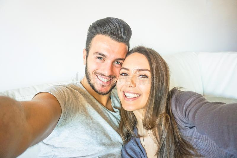 Happy young couple taking a selfie with mobile smart phone camera in the living room embracing on sofa at home royalty free stock photography