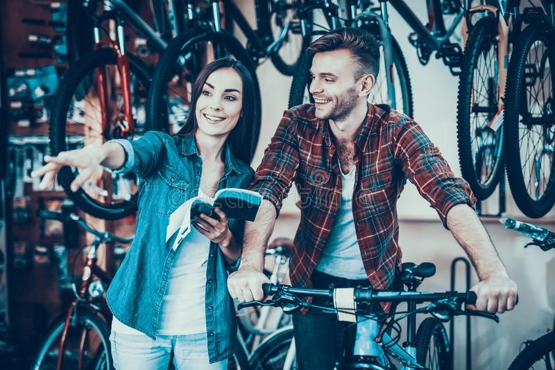 Happy Young Couple Talking While Choose New Bike stock photo