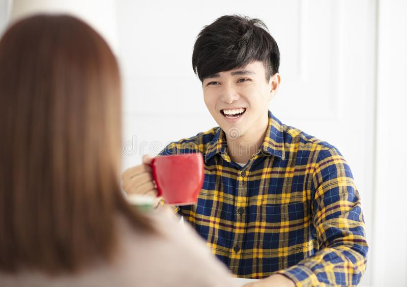 Young couple  talking and laughing, drinking tea royalty free stock images