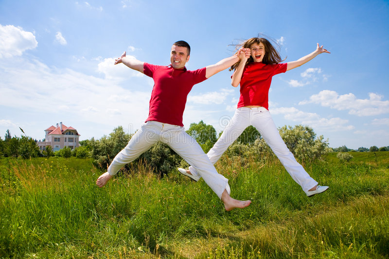 Happy Young Couple - team is jumping in the sky royalty free stock images